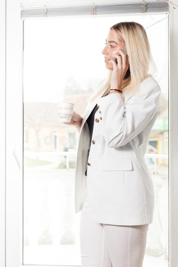 站立在办公室和打电话的女实业家 免版税库存照片