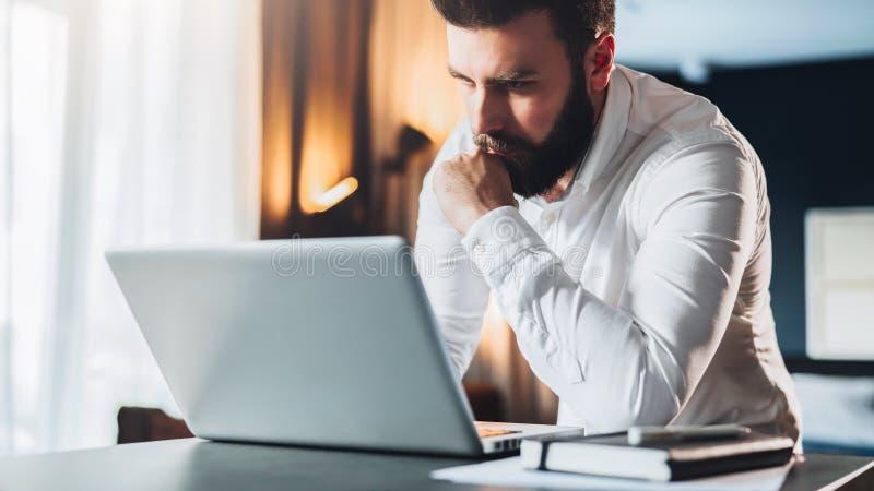 站立在办公室在桌附近和使用膝上型计算机的年轻严肃的有胡子的商人 人研究计算机,检查电子邮件 库存照片