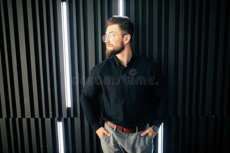 站立在办公室大厅的年轻有胡子的商人画象  免版税图库摄影