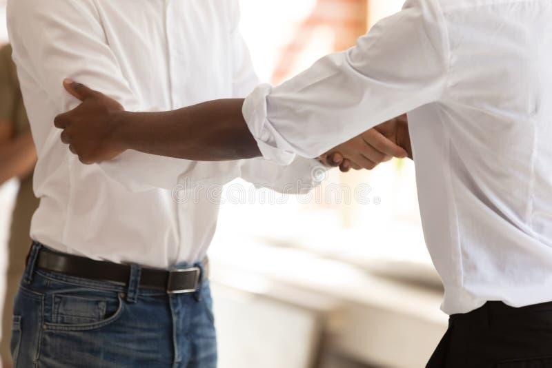 站立在办公室屋子里的不同的商人的关闭握手 免版税库存图片