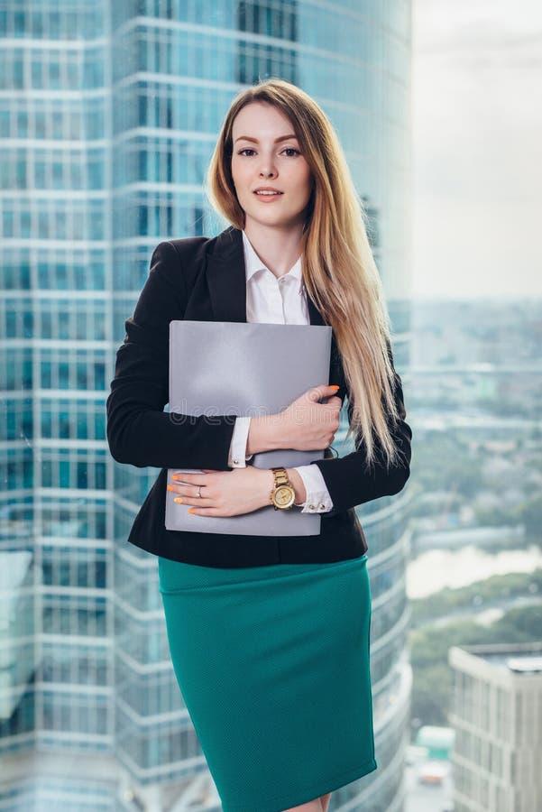 站立在办公室的年轻女性经理在手上拿着一个文件夹反对窗口有在城市商业中心的一个看法 库存照片
