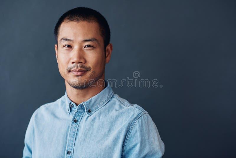站立在办公室的确信和被聚焦的年轻亚裔设计师 库存图片
