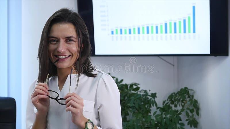 站立在办公室的确信的成熟女实业家 女性经理在看照相机和微笑的办公室 慢的行动 库存图片