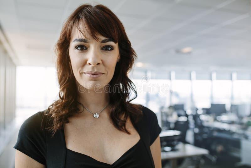站立在办公室的确信的成熟女实业家 免版税库存图片