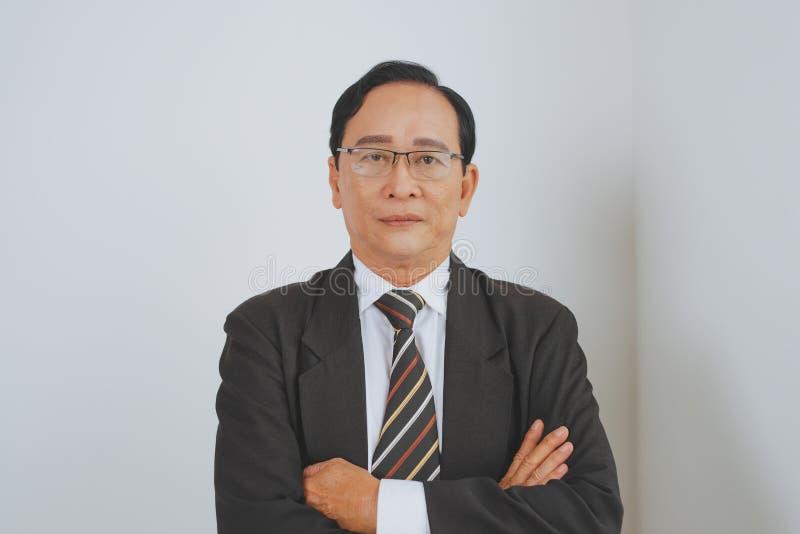 站立在办公室的确信的高级亚洲商业领袖 免版税库存图片