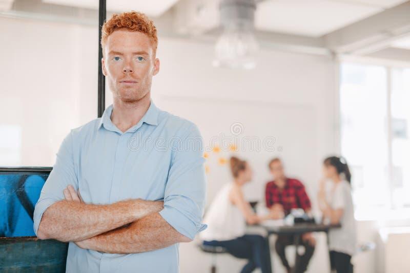 站立在办公室的确信的年轻商人 免版税库存照片