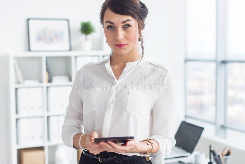 站立在办公室的美丽的女实业家,拿着笔记本,制定计划会议为工作天,看照相机 免版税库存图片