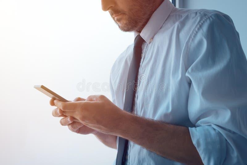 站立在办公室窗口和发短信旁边的商人 免版税库存照片