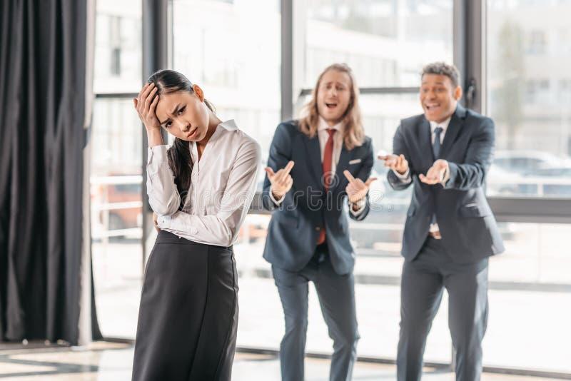 站立在办公室,商人在打手势后和笑的亚裔女实业家 库存图片