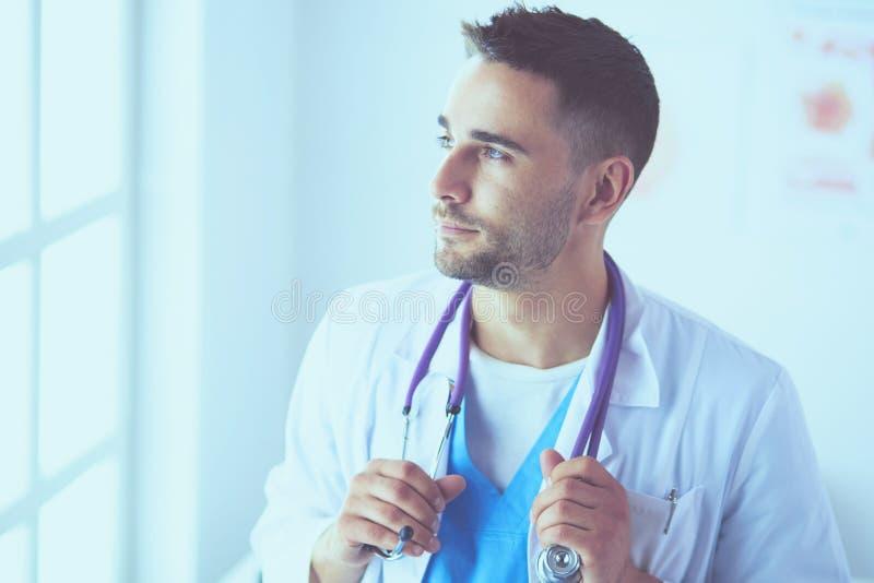 站立在医疗办公室的年轻和确信的男性医生画象 免版税库存照片