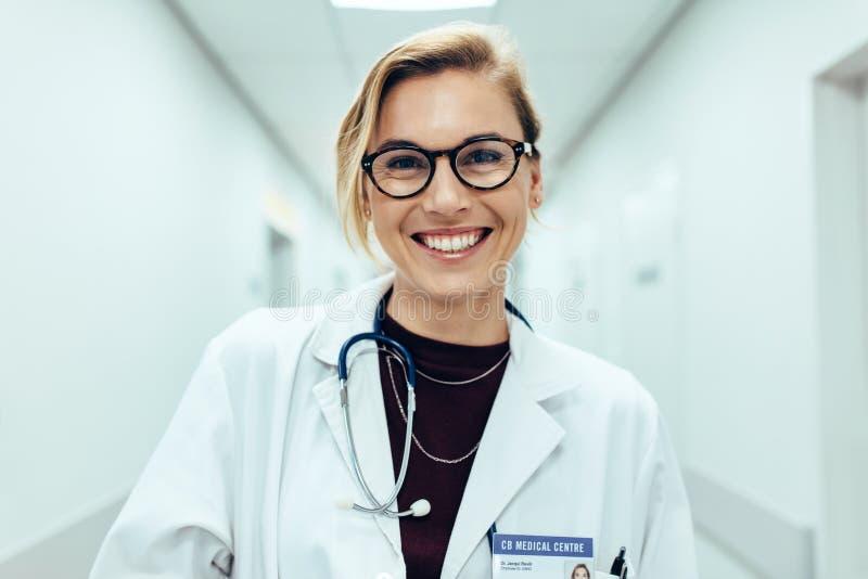 站立在医院走廊的女性医生 免版税库存照片