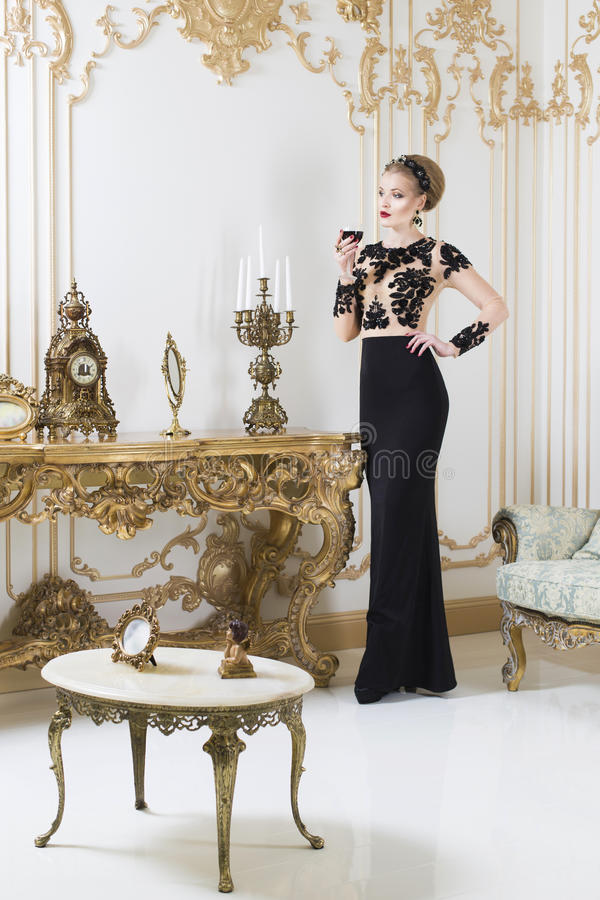 站立在华美的豪华礼服的减速火箭的桌附近的美丽的白肤金发的皇家妇女有杯的酒在她的手上 库存照片