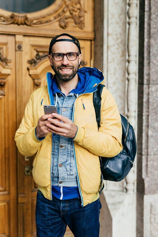 站立在博物馆的时髦衣裳的年轻旅客有愉快的神色在那里 快乐的有胡子的男性在救生服藏品 库存照片