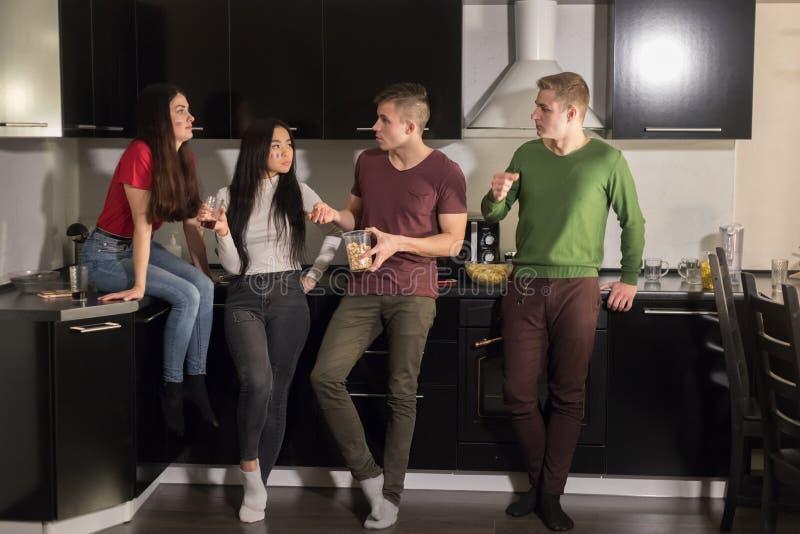站立在厨房和谈话的四年轻人 免版税库存图片