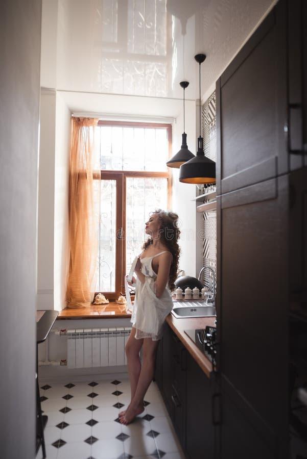站立在厨房里的一个年轻美丽的女孩的剪影在窗口旁边 库存照片