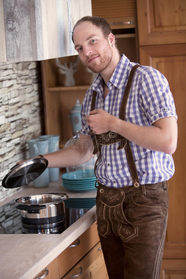 站立在厨房里的传统巴法力亚衣裳的人 免版税库存照片