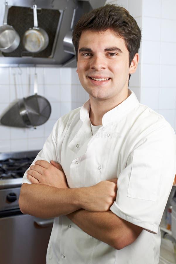 站立在厨房里的男性厨师画象 免版税库存照片