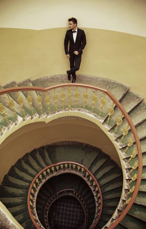 站立在古板的台阶的英俊的典雅的人 免版税图库摄影