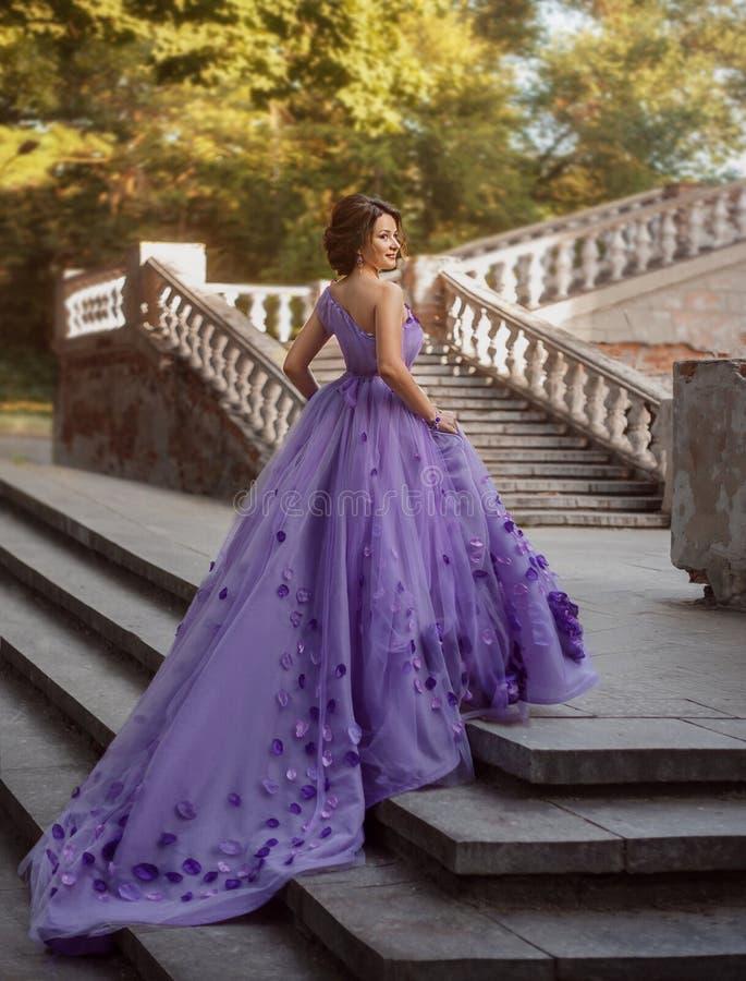 站立在台阶的华美的紫色长的礼服的女孩 免版税库存照片