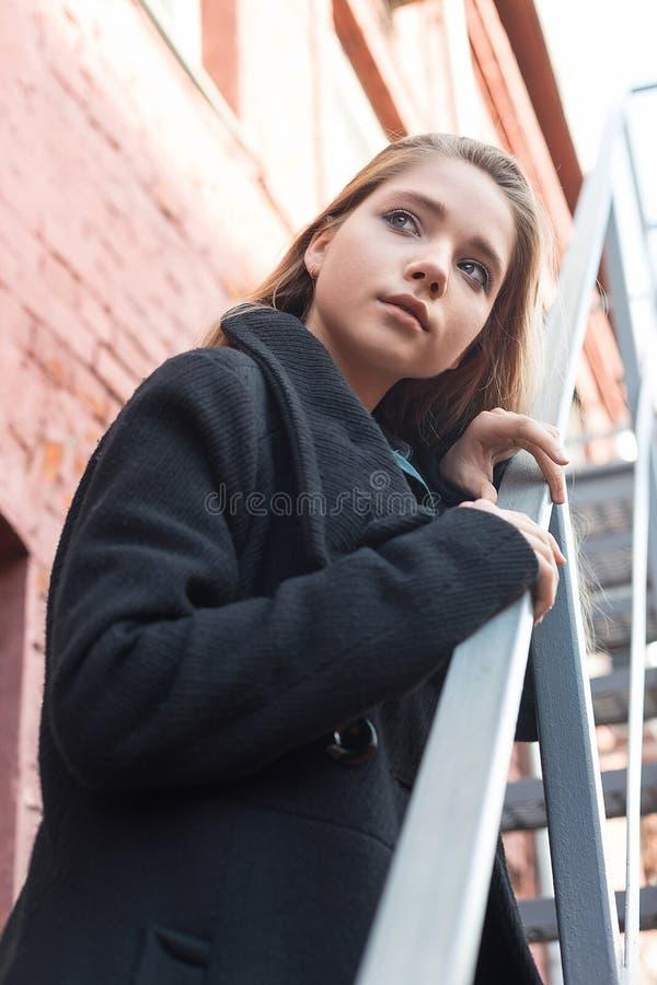 站立在台阶的黑色大衣的少女有在背景的砖墙的 寂寞的概念 免版税库存图片