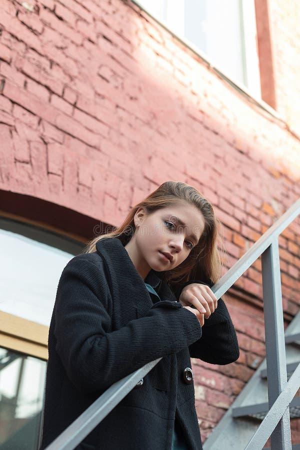 站立在台阶的黑色大衣的少女有在背景的砖墙的 寂寞的概念 库存图片