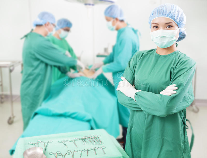 站立在同事前面的外科医生 免版税库存照片
