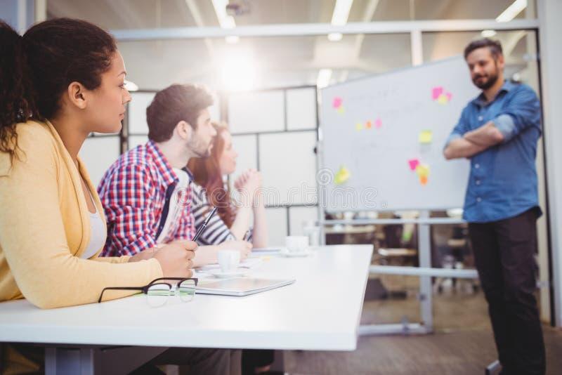 站立在同事前面的执行委员在会议室在创造性的办公室 免版税库存图片