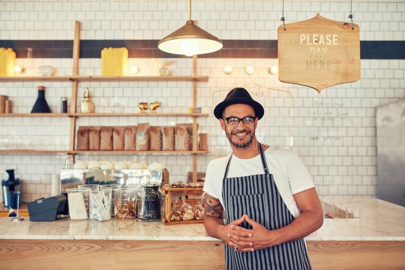 站立在咖啡店的男性barista 免版税库存照片