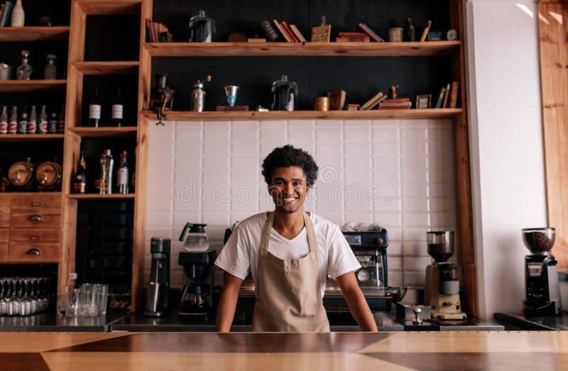 站立在咖啡馆柜台的专业barista 免版税库存图片