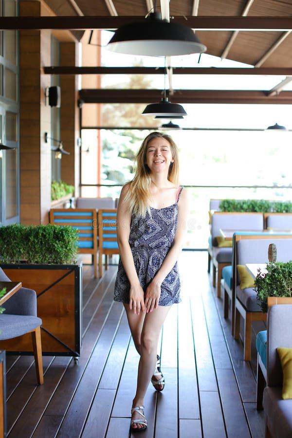 站立在咖啡馆的女性在胳膊椅子和室植物附近 图库摄影