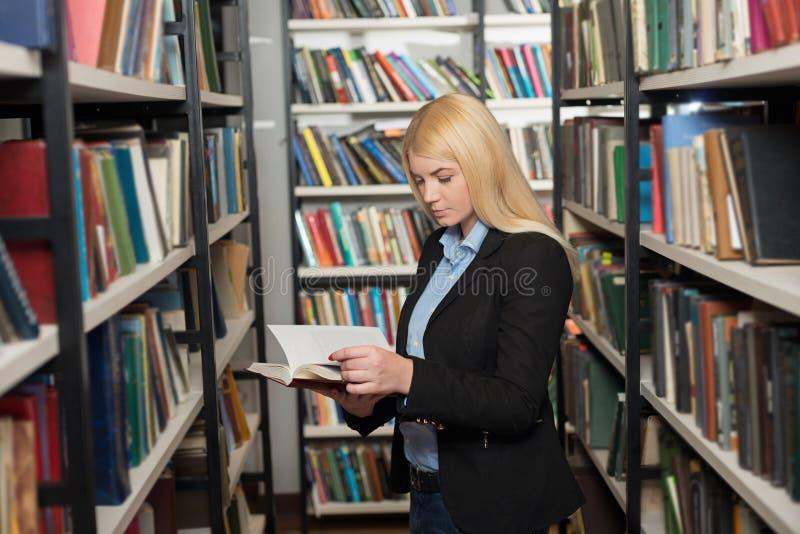 站立在图书馆看的书架之间的小姐 免版税库存照片
