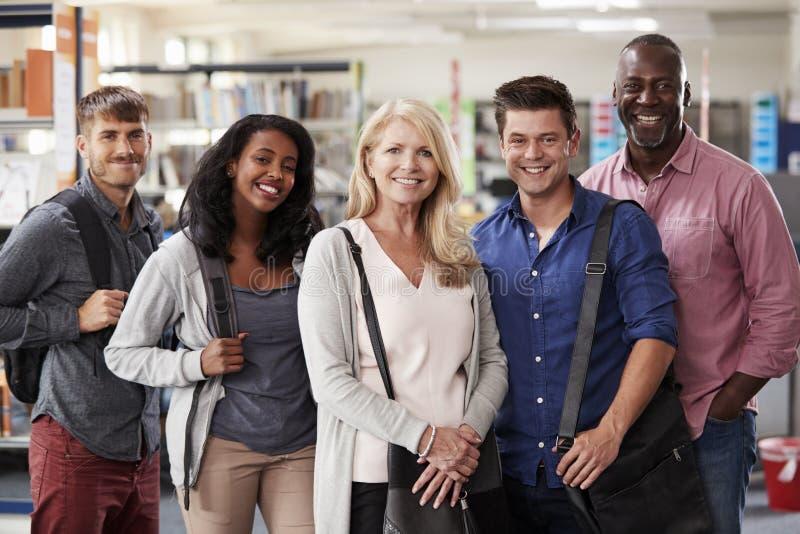 站立在图书馆里的成熟学生团体画象  库存图片