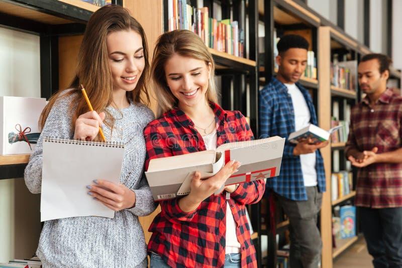 站立在图书馆阅读书的微笑的女学生 免版税库存照片