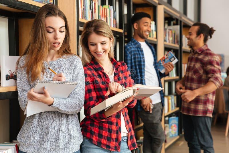 站立在图书馆阅读书的微笑的女学生 免版税库存图片