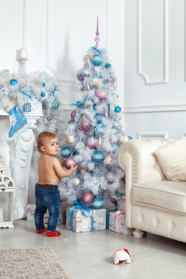 站立在圣诞树附近的女婴 图库摄影