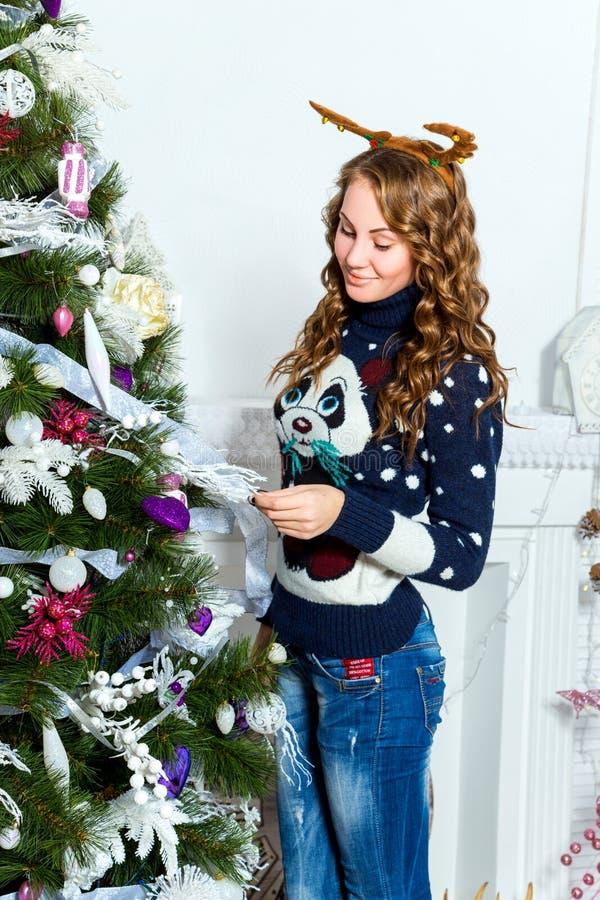 站立在圣诞树附近的美丽的女孩在一个绝尘室 库存照片