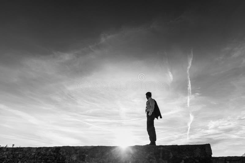 站立在地平线的商人的单色图象 免版税库存照片