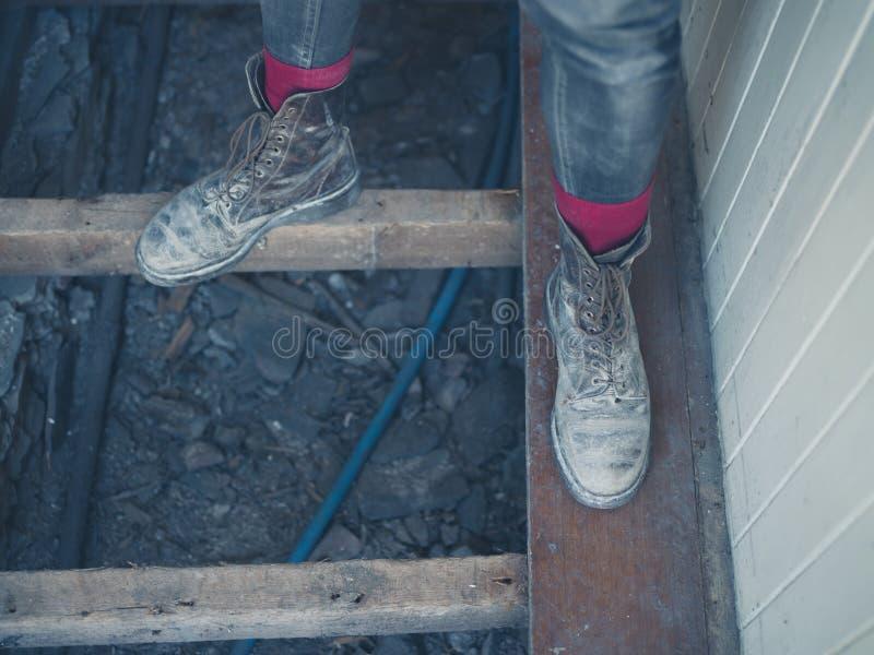 站立在地板安装托梁的工作者的脚 库存图片