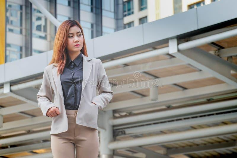 站立在城市的美丽的年轻女实业家画象  免版税库存图片