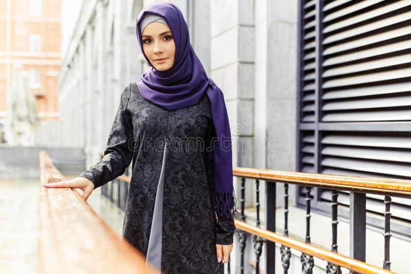 站立在城市街道上的传统东方衣裳的美丽的伊斯兰教的妇女 免版税库存照片