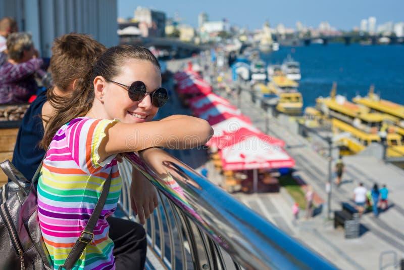 站立在堤防的微笑的少年学生女孩在附近 免版税库存照片