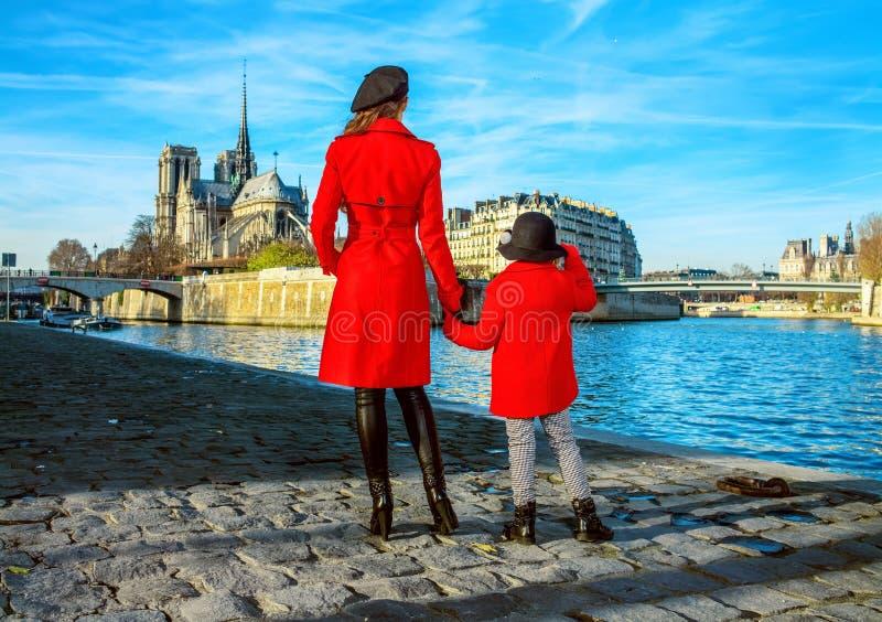 站立在堤防的母亲和儿童旅行家在巴黎 免版税库存图片