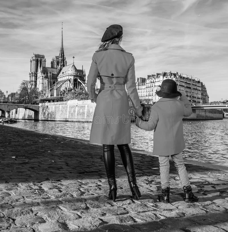站立在堤防的母亲和儿童旅行家在巴黎 图库摄影
