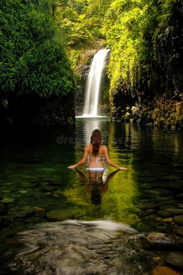 站立在塔韦乌尼岛的Wainibau瀑布的比基尼泳装的少妇 免版税库存图片