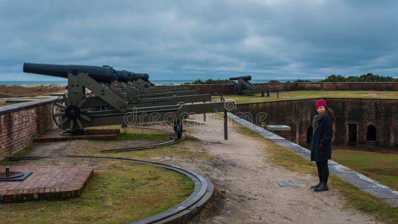 站立在墙壁上的大炮前面的南北战争堡垒的妇女 库存图片