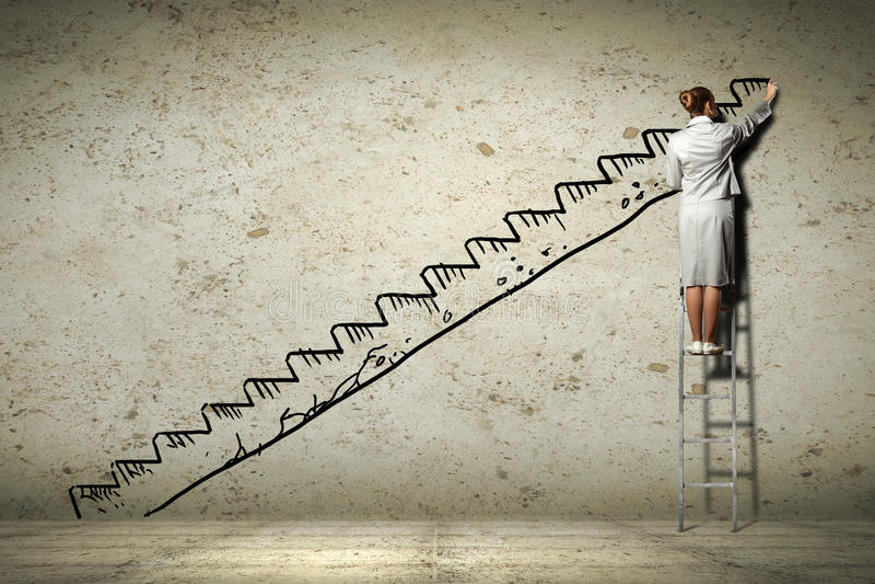 站立在墙壁上的梯子图画的妇女 免版税图库摄影