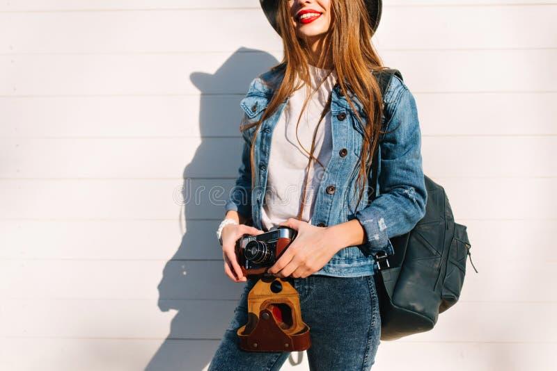 站立在墙壁前面的夹克的微笑的女性摄影师准备好做新的照片 可爱的年轻深色的妇女 免版税库存照片