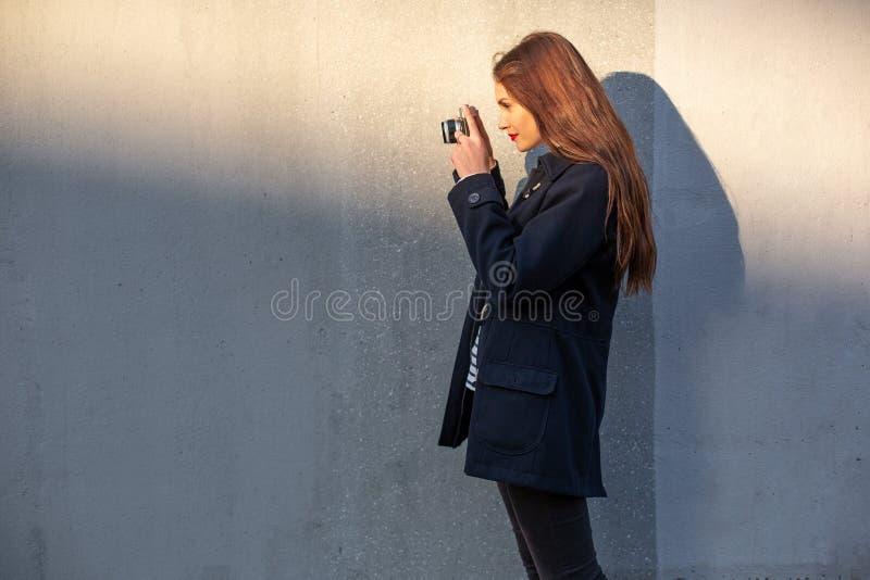 站立在墙壁前面的夹克的微笑的女性摄影师准备好做新的照片 库存图片