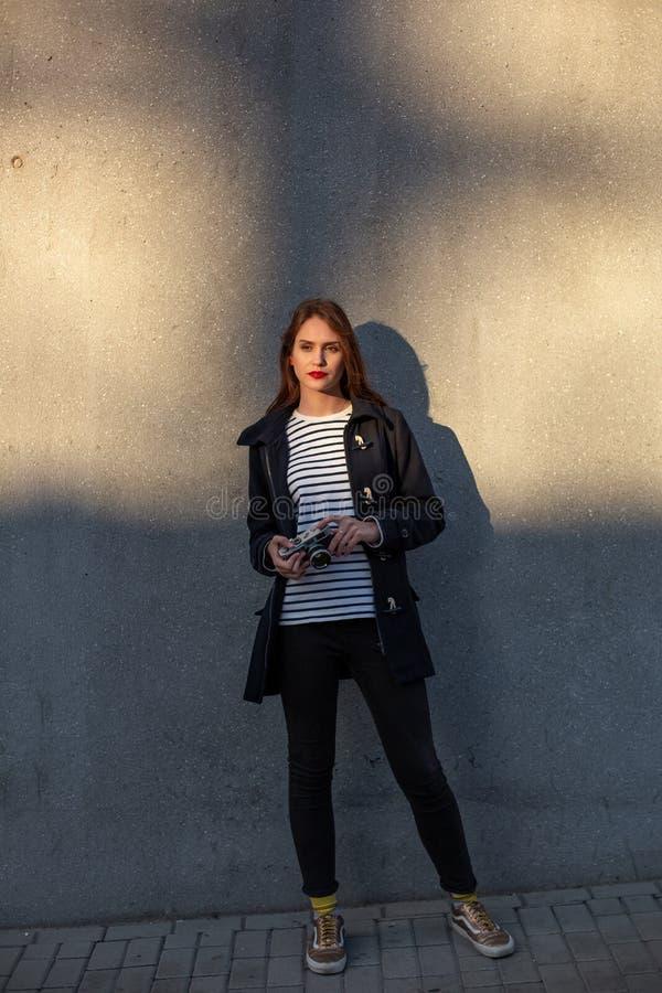 站立在墙壁前面的夹克的微笑的女性摄影师准备好做新的照片 库存照片