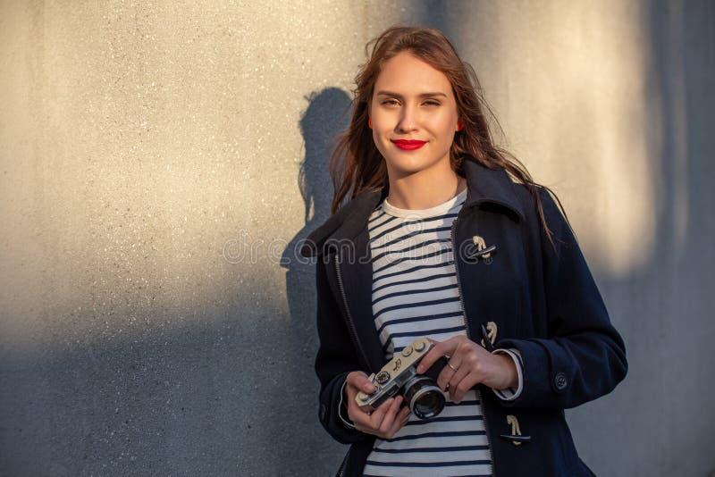 站立在墙壁前面的夹克的微笑的女性摄影师准备好做新的照片 免版税库存照片